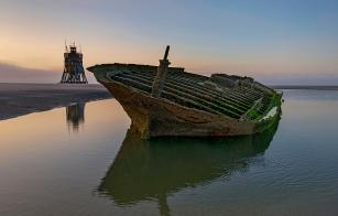 Wrack des gestrandeten Seglers Ulpiano im Wasser dahinter die Rettungsbake auf der Sandbank Suedeoogsand. Im Nationalpark Nordfreisisches Wattenmeer gelegen.